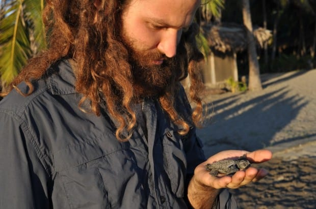 Aaron contemplates his connection to a new baby turtle.